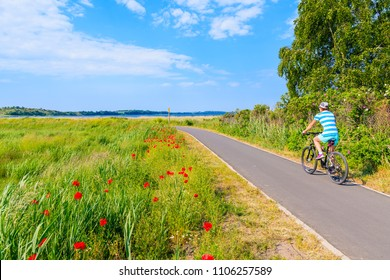 Young woman cyclist riding bicycle on route from Baabe to Moritzdorf village in countryside spring landscape, Ruegen island, Baltic Sea, Germany