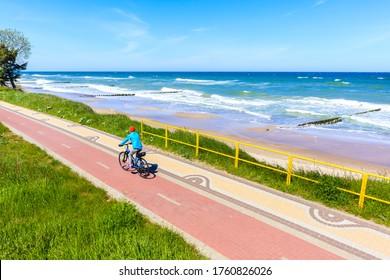 Young woman cyclist riding bike along beautiful beach with near Kolobrzeg town, Baltic Sea coast, Poland