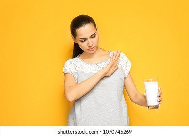 Young woman with dairy allergy holding glass of milk on color background