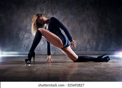 Young woman dancer in black clothing on wall background.