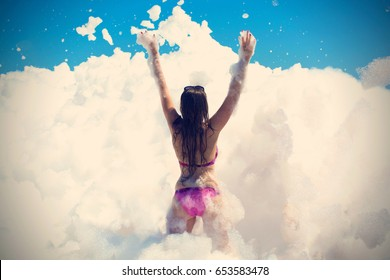 Young woman dances and raised her hands at a foam party at the beach