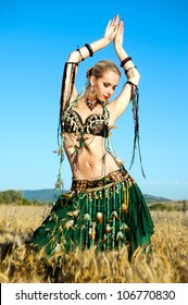 young woman dances tribal in the field of wheat