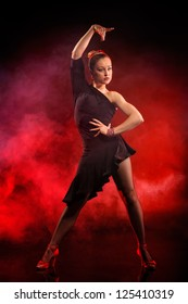 young woman dancing flamenco on dark red background