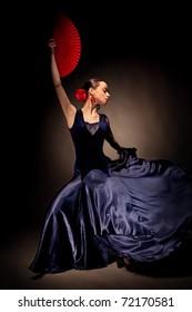 young woman dancing flameno on black