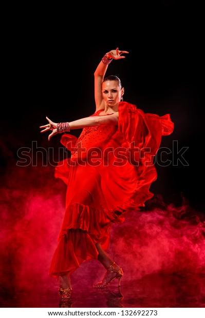 Young woman dancing Latino on dark smoky background.