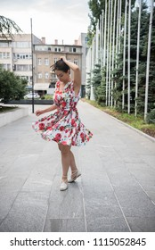 young woman dancing on street in colorful dress