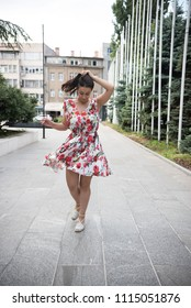 young woman dancing and smiling on street