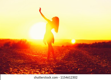 young woman dancing at sunset on the beach