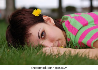 young woman with dandelion lying on green grass in spring park