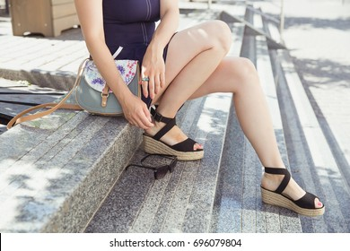 Young woman in  dark blue dress and black espadrille wedge sandals sitting on the stairs. Leather handbag of gray color with an insert of floral design and black sunglasses are part of the summer look
