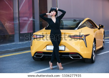 Young woman with dark hair in black bodysuit and sunglasses posing near  supercar. Portrait of 2a56f8a97