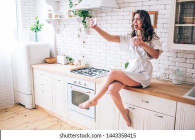 Young woman with dark hair sitting on tabletop in kitchen. Taking selfie and showing tounge on camera. Alone in kitchen. Morning daylight. Wear beautiful gown.