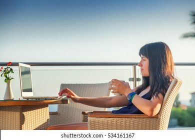 young woman with dark hair sitting at the table with a cup of coffee and a laptop on the background of the sea