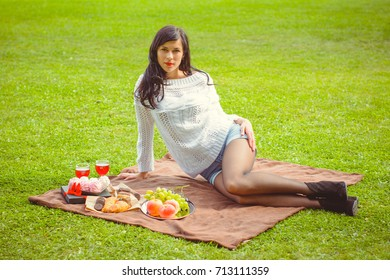 A young woman with dark hair in a white sweater at a picnic is resting on the green grass and is having a rest this afternoon. Beauty of nature and relax at sunny day
