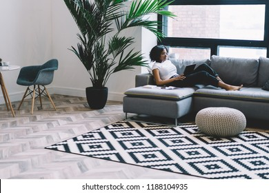 Young woman with dark skin relaxing on comfortable sofa and reading news on network using high speed home internet on touch pad. African American shopping online, convenience remote work on freelance