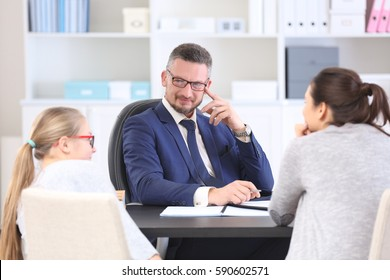 Young woman with daughter during teacher-parent meeting at school