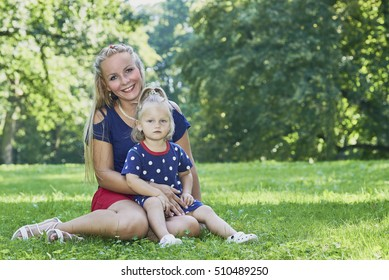 Young woman with daughter sitting on the grass in the park