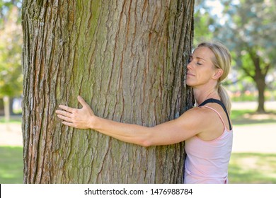 Young woman daydreaming about nature and ecology with closed eyes while hugging a tree trunk outdoors in the park in a sunny day of summer