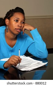 A young woman daydreaming while going over some forms.