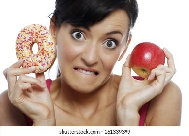 Young woman deciding between an apple or doughnut.