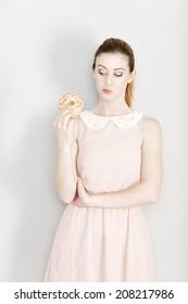 Young woman deciding whether to eat an unhealthy doughnut expressing guilt.
