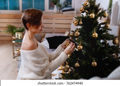 Young woman is decorating the xmas tree creating holiday atmosphere
