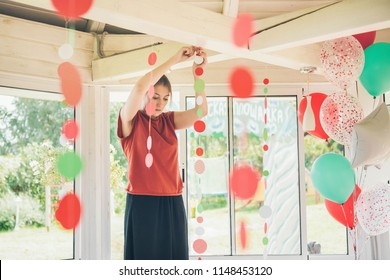 Young woman decorator hanging up paper garlands to preparing the children's birthday party. The party planner.