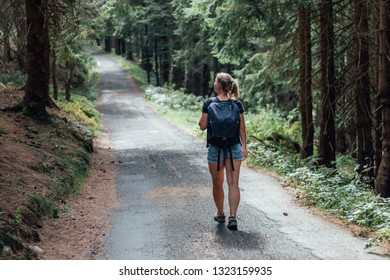 Young woman in denim shorts walking on asphalt road in summer coniferous forest. Girl with black backpack hiking in Krkonose national park, Czech Republic.