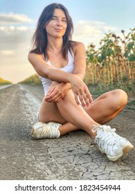 Young woman in denim shorts and a white T-shirt sits on dirt road