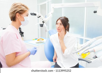 Young woman at the dentist complaining about a toothache. Dentistry. Doctor and the patient