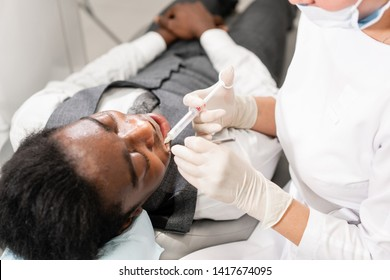 Young woman dentist treating root canals in the dental clinic. Young African American male with bad teeth lying on dentist chair with open mouth.