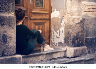 Young woman depressed. Sad young woman in depression. Girl sitting alone on the doorstep. Depression. Depression. Sadness. Loneliness. Solitude.