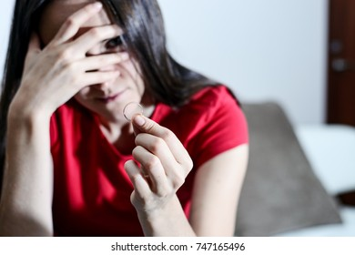 Young woman in depression with a wedding ring in hand close up. Mourning after a divorce. Selective focus.