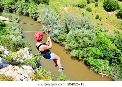young woman descending on a zip-line (flying fox)