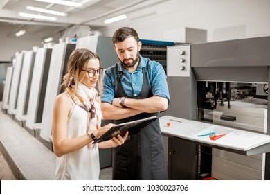 Young woman designer and print operator working together at the print manufacturing with offset machine on the background
