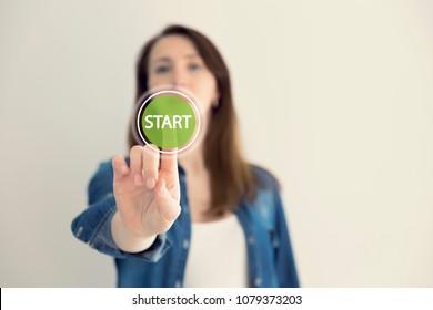 Young woman designer touching virtual button start. New start, beginning, business concept