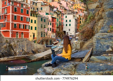 A young woman digital nomad working on the laptop in Italy, in the little town Riomaggiore in Cinque Terre, as a symbol of financial freedom, traveling around the world and early retirement
