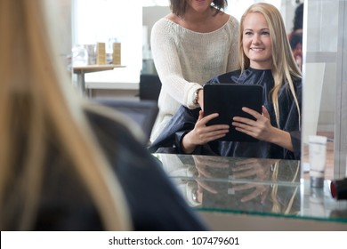 Young woman with digital tablet showing hairstyle to hair dresser