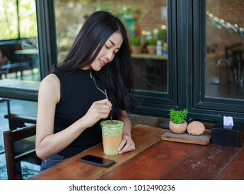 young woman dinking ice green tea latte in the cafe