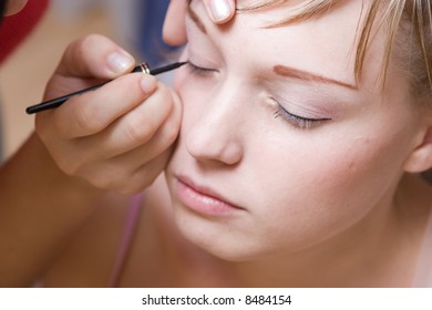 The young woman directs a make-up in the morning before wedding