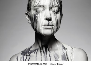 Young woman with Dirty Face. liquid paint flowing over a beautiful face and Body. Girl in Paint