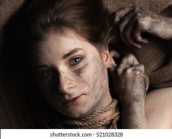 Young woman with dirty face and rope on jute background