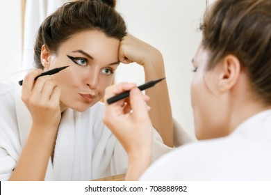 Young woman is disappointed with her skill of applying makeup