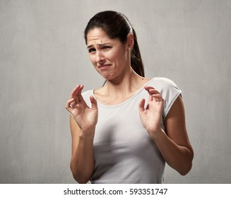 Young woman disgusted squeamishness over gray wall background