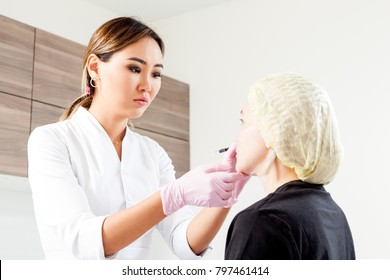 Young woman doctor beautician in white lab coat and sterile gloves draws a marking on woman's cheekbones before injecting Botox to correct forms