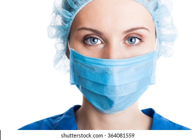 Young woman doctor in cap and face mask isolated on white