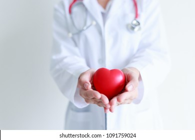 Young woman doctor holding a red heart with white background