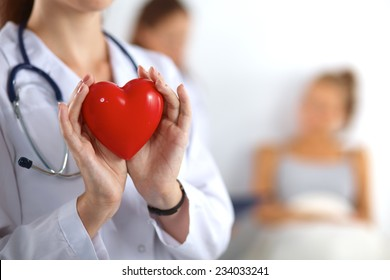 Young woman doctor holding a red heart, isolated on white
