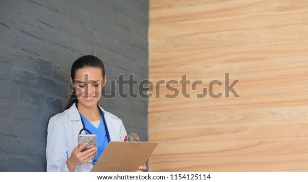 Young woman doctor sitting with your phone. Woman doctors.