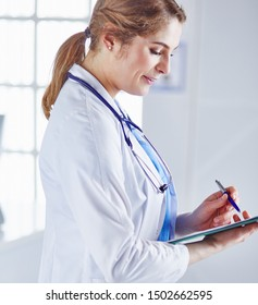 Young woman doctor is standing with board with clipboard smilin